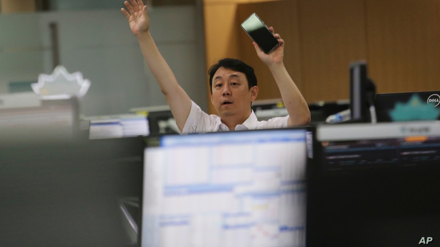 A currency trader gestures at the foreign exchange dealing room of the KEB Hana Bank headquarters in Seoul, South Korea,…