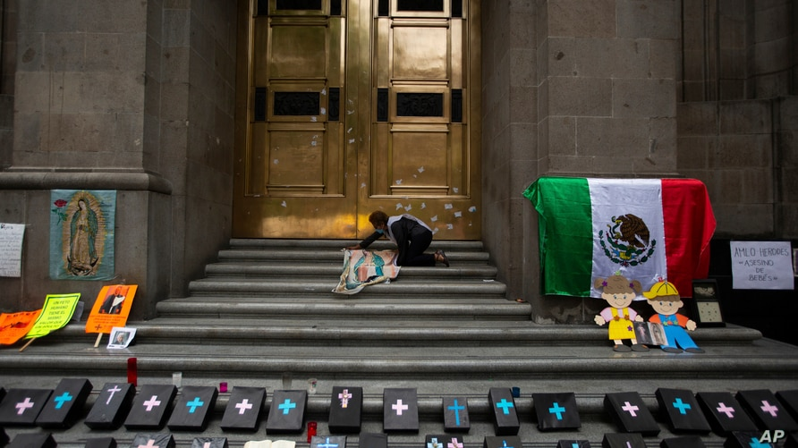 An activist against abortion places an image of Our Lady of Guadalupe alongside small, mock coffins at the entrance to the…