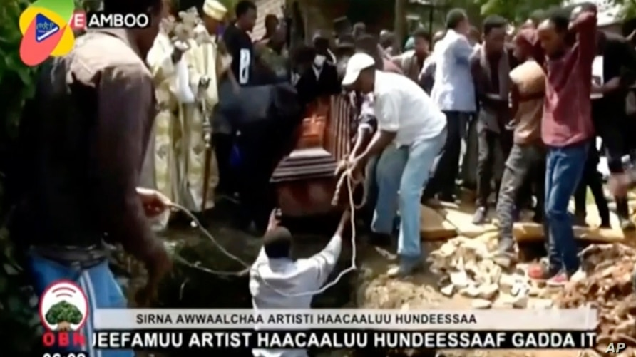 In this image taken from OBN video, the coffin carrying Ethiopia singer Hachalu Hundessa is lowered into the ground during the…