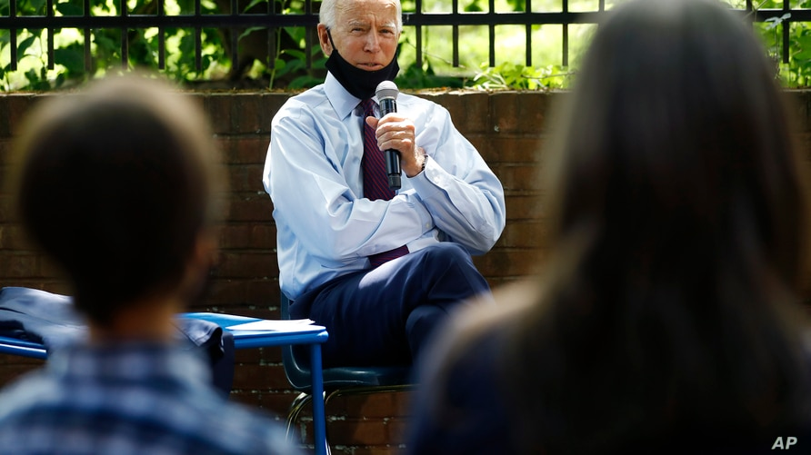FILE - In this June 25, 2020, file photo, Democratic presidential candidate former Vice President Joe Biden, center, speaks to…