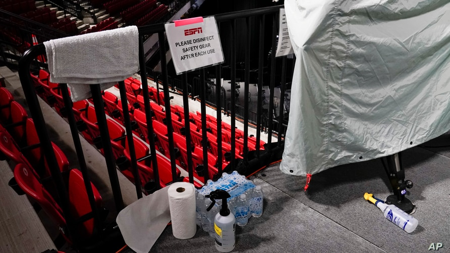 Disinfectant spray sits near television cameras inside a basketball arena at ESPN Wide World of Sports Complex Wednesday, July…