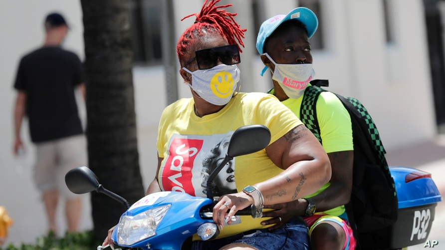 People wearing protective face masks ride a scooter down Ocean Drive during the coronavirus pandemic, Sunday, July 12, 2020, in…