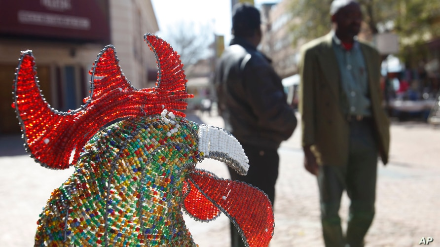 In this photo taken July 30, 2009 , pedestrians pass a wire and beaded cock on display outside the Market Theater, background,…