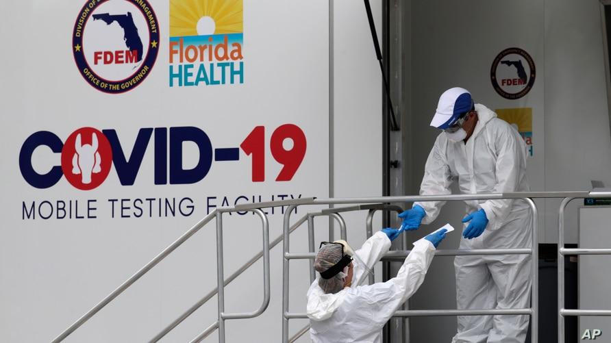 Health care workers work at a walk-up COVID-19 testing site during the coronavirus pandemic, Friday, July 17, 2020, in Miami…