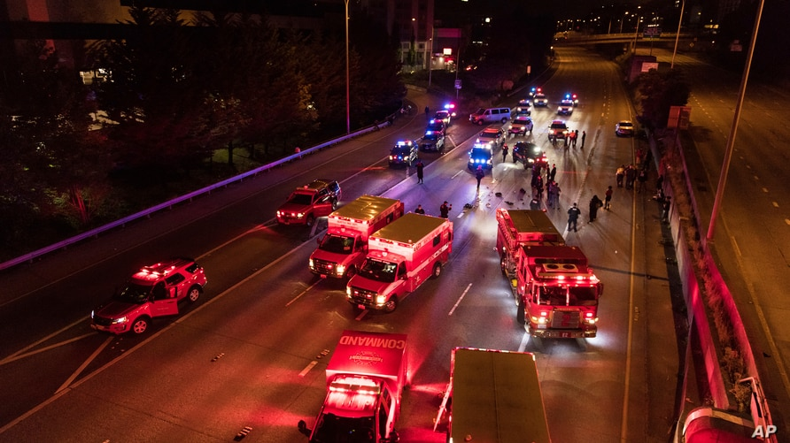 Emergency personnel work at the site where a driver sped through a protest-related closure on the Interstate 5 freeway in…