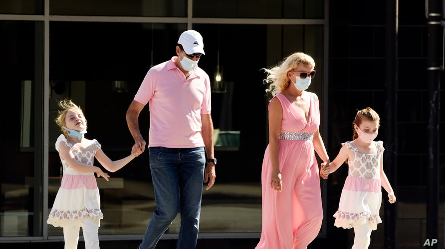 Pedestrians wear masks as they cross Brand Boulevard, Thursday, July 23, 2020, in Glendale, Calif. Three out of four Americans,…