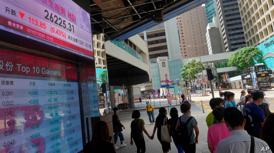 People wearing face masks walk in front of a bank's electronic board showing the Hong Kong share index at Hong Kong Stock…