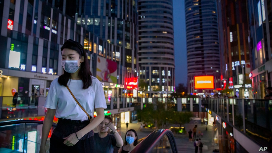 People wearing face masks to protect against the coronavirus ride an escalator at a shopping and office complex in Beijing,…