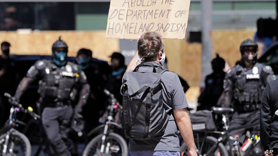 A protester holds up a sign toward police officers Sunday, July 26, 2020, in Seattle, where a small group of demonstrators…