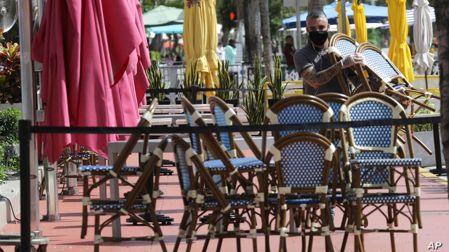 An employee at the Clevelander bar and restaurant on Ocean Drive stacks chairs as they have shut down due to public health…
