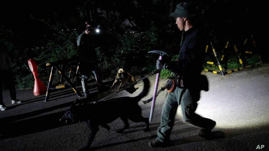 South Korean police officers with dogs leave to search for missing Seoul Mayor Park Won-soon in Seoul, South Korea, Thursday,…