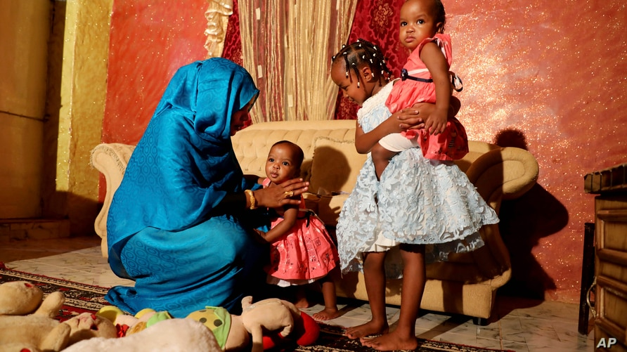 Youssria Awad plays with her daughters in their home, in Khartoum, Sudan on  June 14, 2020. She refuses to carry out female…