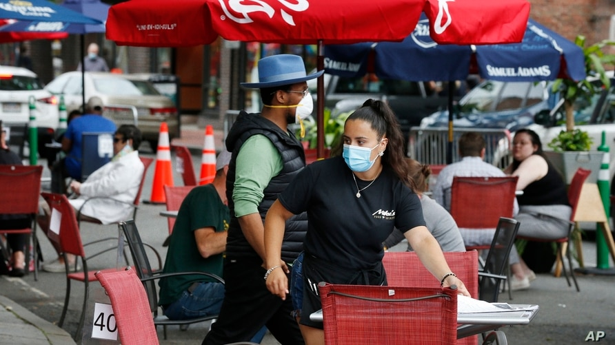 A waitress seats customers at a restaurant with outdoor dining on a section of street closed to traffic to promote social…