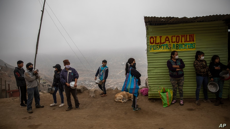 """Residents wait in line at a """"community pot,"""" in the Nueva Esperanza neighborhood of Lima, Peru, Wednesday June 17, 2020. For…"""