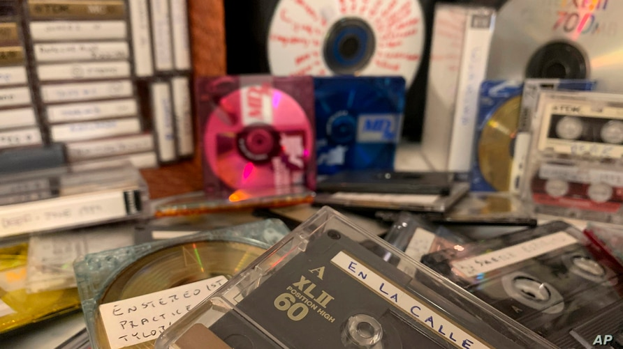 A stack of cassettes, MiniDiscs and CDs representing some of AP journalist Jaime Holguin's decades-rich audio archive sit on a…