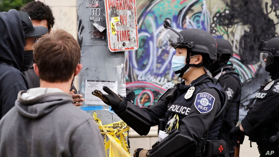 A police officer engages with a protester Wednesday, July 1, 2020, in Seattle, where streets had been blocked off in an area…