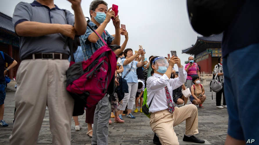 Parents wearing face masks to protect against the coronavirus take photos of students as they pose for a group photo at the…