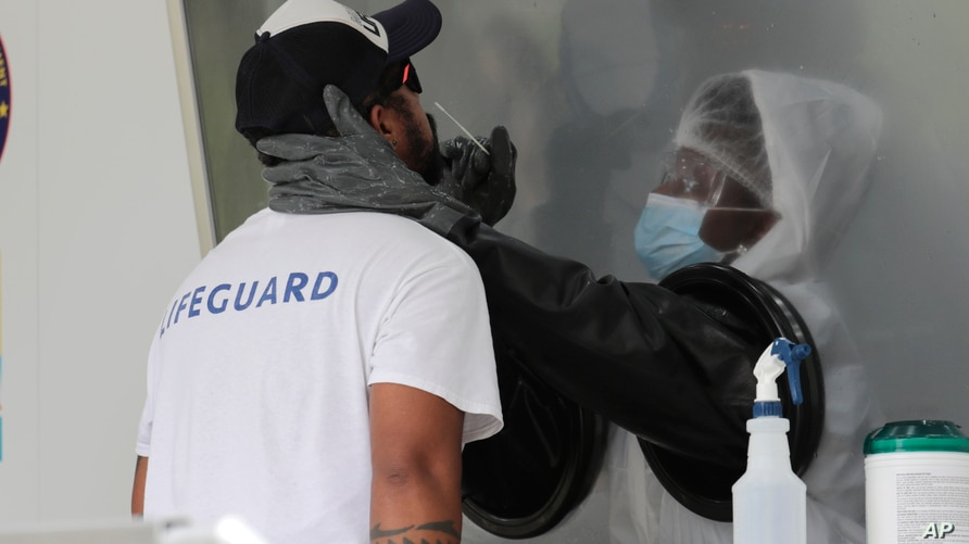 Rafael Ruiz, left, is tested for COVID-19 at a walk-up testing site during the coronavirus pandemic, Friday, July 17, 2020, in…