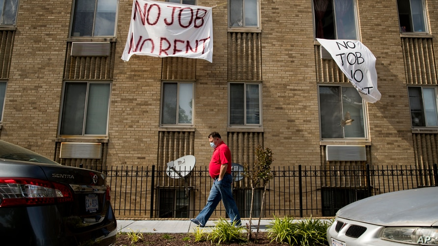 "FILE - In this May 20, 2020 file photo, signs that read ""No Job No Rent"" hang from the windows of an apartment building in…"