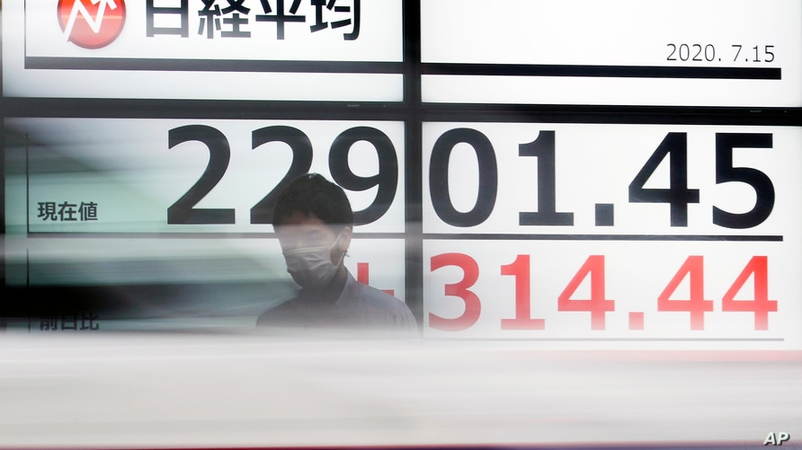 A man stands in front of an electronic stock board showing Japan's Nikkei 225 index at a securities firm as a car passes by in…