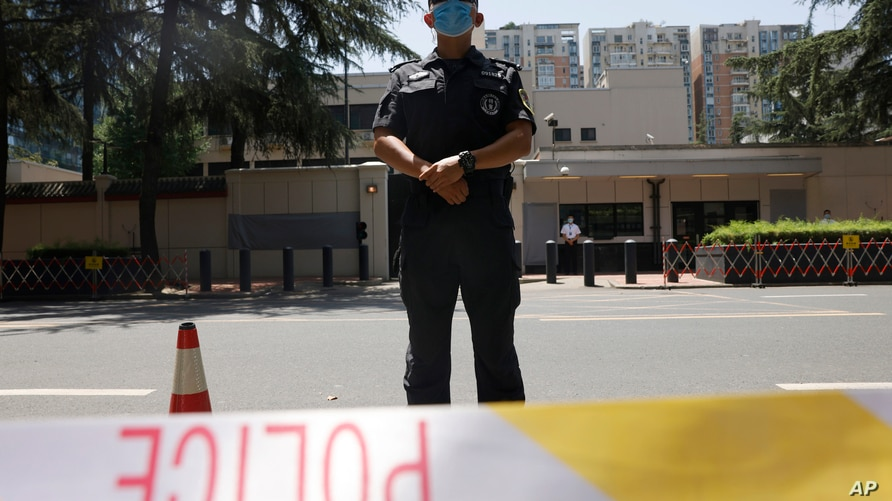 Chinese police officers guard the former United States Consulate that was closed in Chengdu in southwest China's Sichuan…