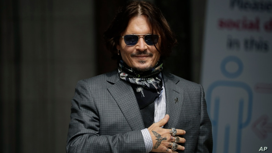 U.S. actor Johnny Depp gestures to fans and the media as he arrives at the High Court in London, Thursday, July 23, 2020. Depp…