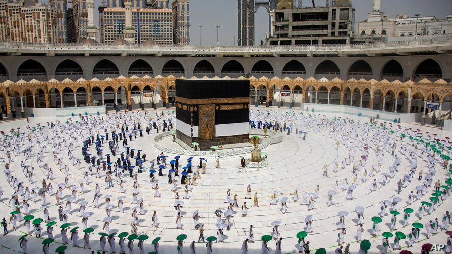 In this photo released by the Saudi Media Ministry, limited numbers of pilgrims, move several feet apart, circling the cube…