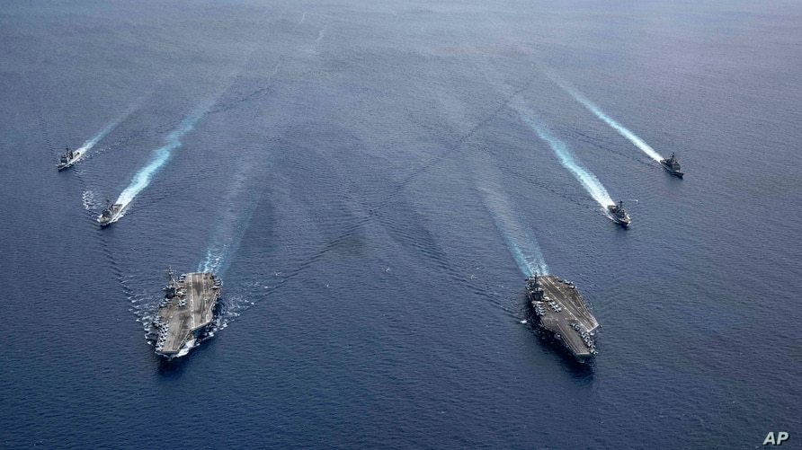 In this photo provided by U.S. Navy, the USS Ronald Reagan (CVN 76) and USS Nimitz (CVN 68) Carrier Strike Groups steam in…