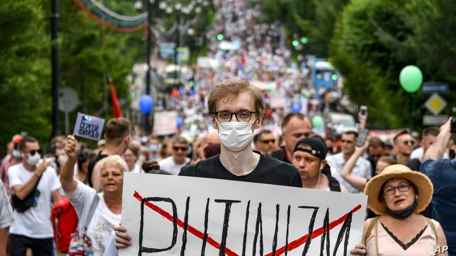 """A man holds poster reading """"Putinizm """" during an unsanctioned protest in support of Sergei Furgal, the governor of the…"""