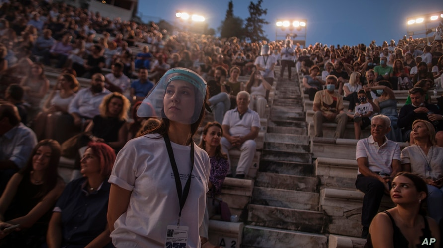 An usherette wearing a face shield stands in front of the audience at the Odeon of Herodes Atticus in Athens, Greece, after the…