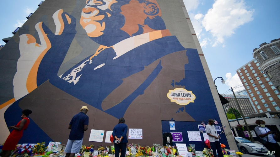 People gather at a make-shift memorial near the home of Rep. John Lewis, D-Ga., Sunday, July 19, 2020, in Atlanta. Lewis, who…