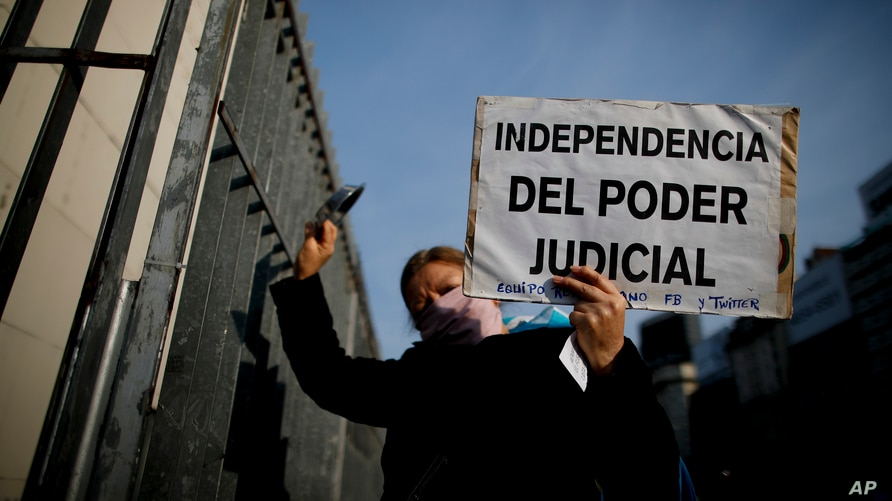 """A woman holds a poster with a message that reads in Spanish: """"Independence of judicial power"""" during a protest against a…"""