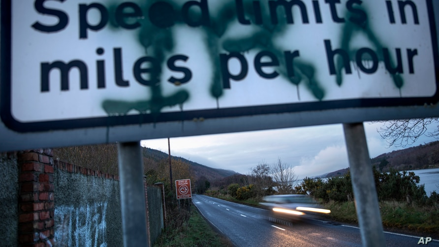 A sign on the border between Northern Ireland and the Republic of Ireland, spray painted with the initials of the Irish…