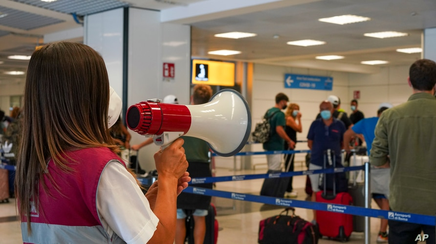 Passengers arriving in Rome from four Mediterranean countries receive instructions by airport staff, right, as they line up…