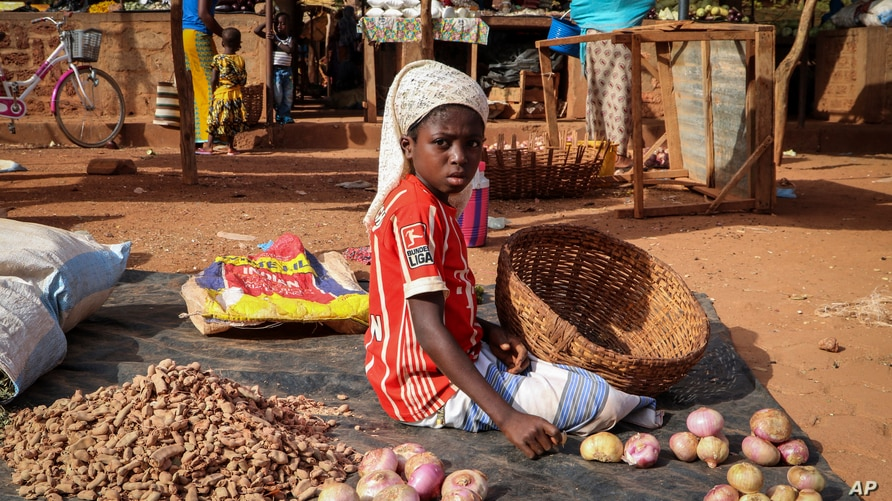 In this Wednesday, May 13, 2020, photo, a child sits on the ground selling onions at a market stall in Tougan, Burkina Faso…