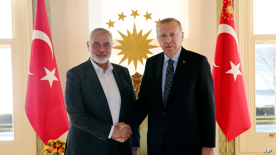 Turkey's President Recep Tayyip Erdogan, right, shakes hands with Hamas movement chief Ismail Haniyeh, prior to their meeting…