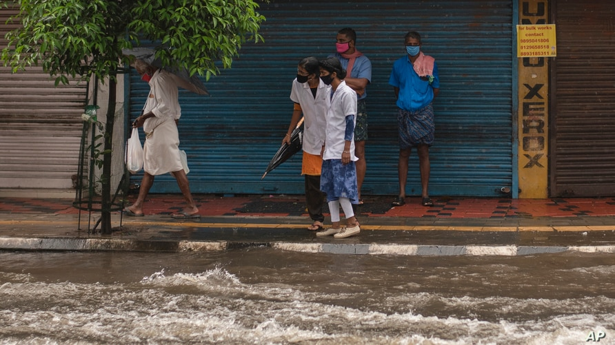 Two medical workers wearing masks as a precaution against the coronavirus assess the water level as they try to cross a flooded street during heavy rainfall in Kochi, Kerala state, India, Aug. 7, 2020.
