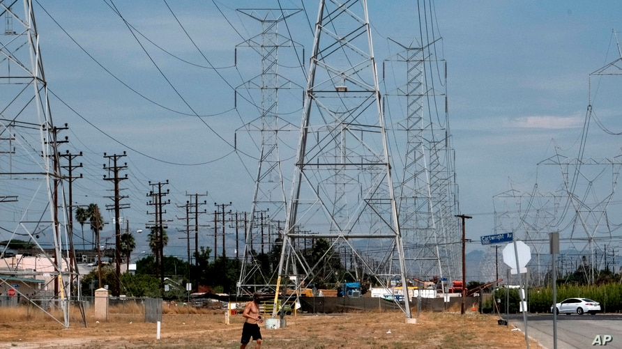 A jogger runs in extreme heat under high tension electrical lines in the North Hollywood section of Los Angeles on Saturday,…