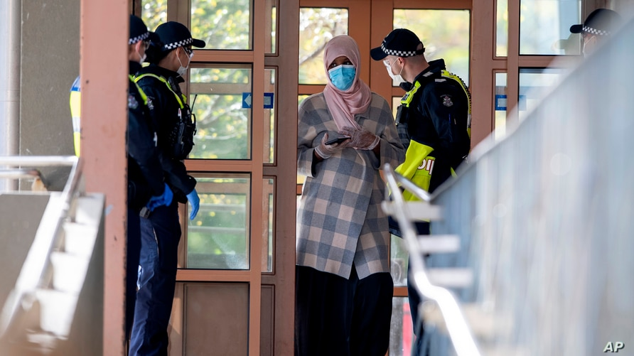 Police talk to a woman at housing commission apartments under lockdown in Melbourne, Australia, on Monday, July 6, 2020. The…