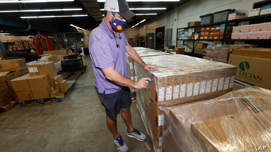 Jason Rand cuts open the shrink wrap around a pallet of Lenovo Chromebook laptops as they sit in a Denver Public Schools…