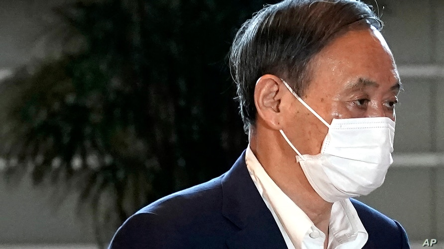 Japan's Chief Cabinet Secretary Yoshihide Suga wearing a face mask walks to attend Prime Minister Shizo Abe's press conference…