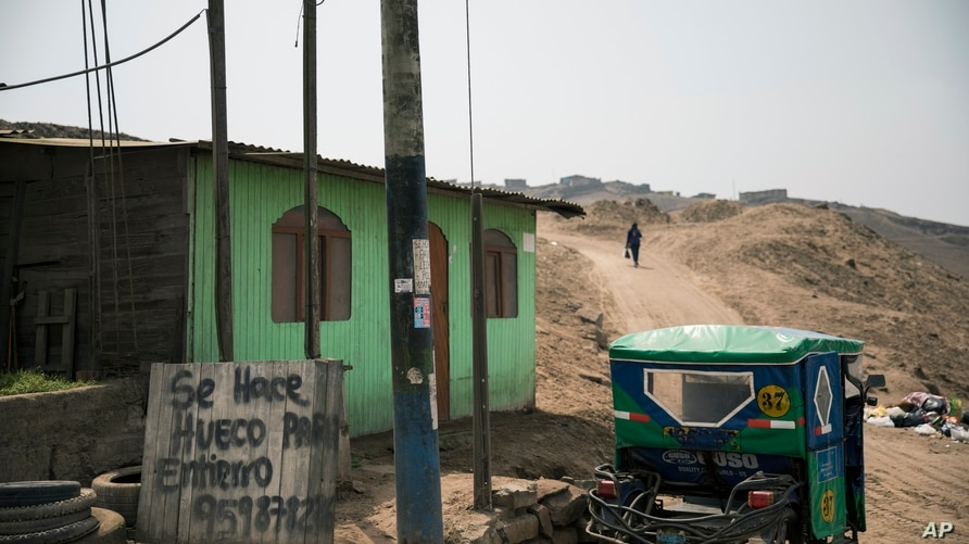 """A woman walks near a sign that reads in Spanish """"I made holes for burials,"""" near a cemetery in Ventanilla, on the outskirts of…"""