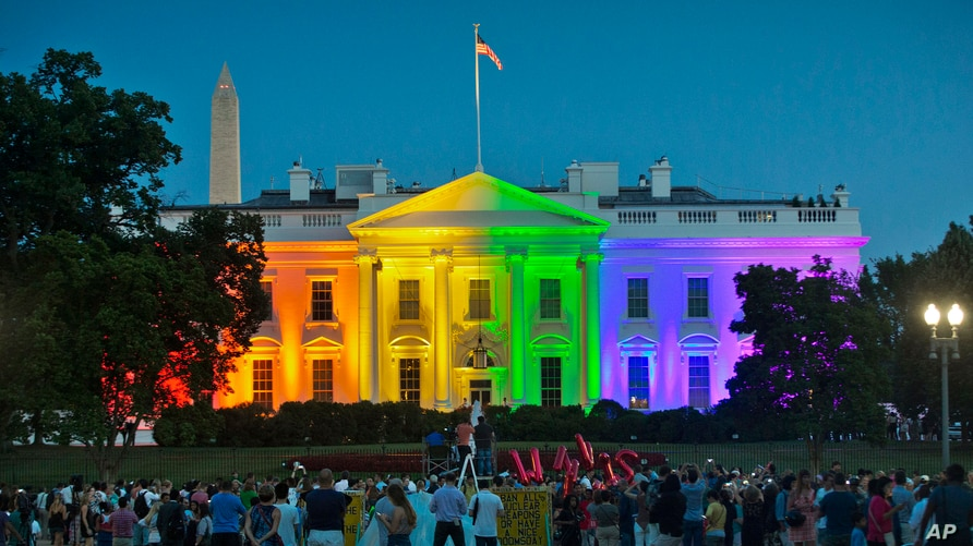 FILE - In this Friday, June 26, 2015 file photo, people gather in Lafayette Park to see the White House illuminated with…