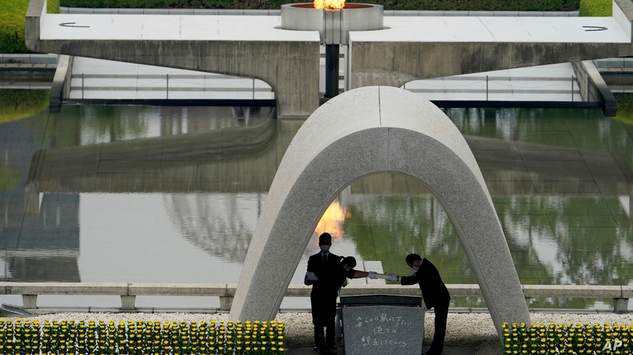 Kazumi Matsui, right, mayor of Hiroshima, and the family of the deceased bow before they place the victims list of the Atomic…