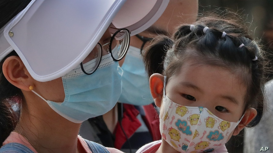 A woman and a child wearing face masks to protect against the new coronavirus visit a shopping mall in Beijing, Sunday, Aug. 2,…