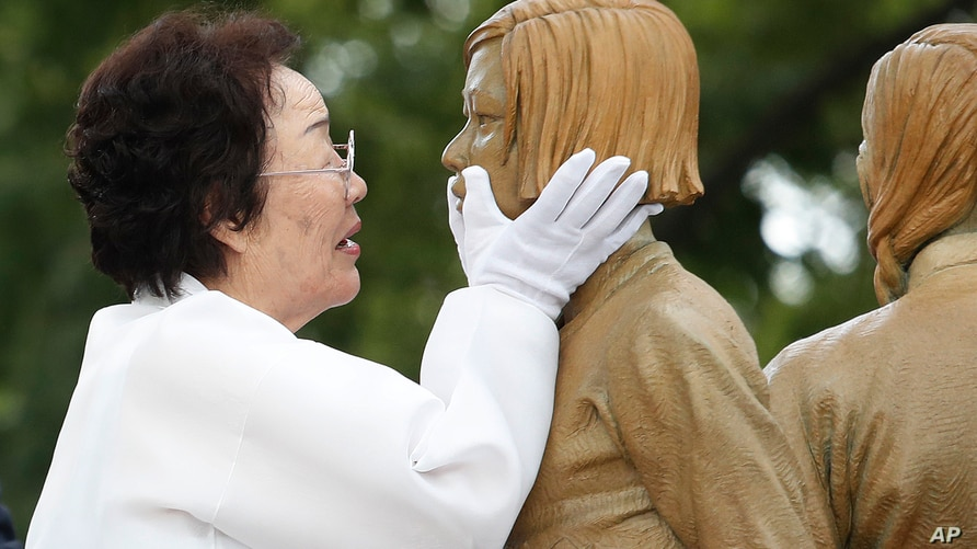 Lee Yong-soo who was forced to serve for the Japanese troops as a sex slave during World War II, touches the face of a statue…