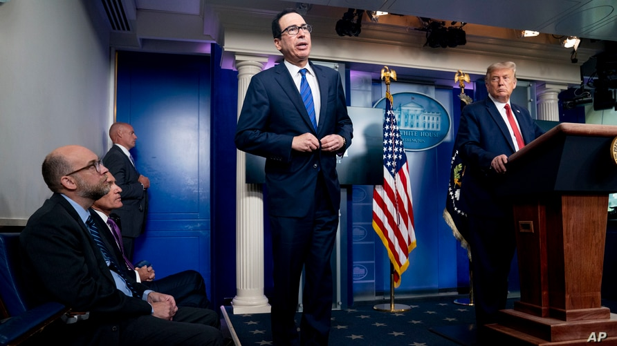 President Donald Trump listens as Treasury Secretary Steven Mnuchin speaks at a news conference in the James Brady Press…