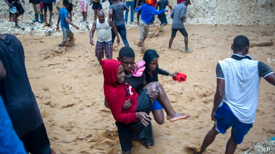 A man carries a woman across the Tet Dlo river during the passing of Tropical Storm Laura in Port-au-Prince, Haiti, Sunday, Aug…