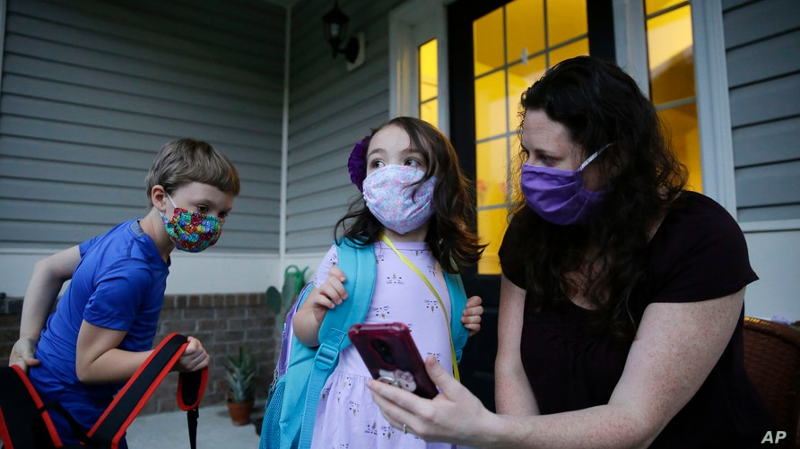 Rachel Adamus, right, shows her children, Paul, left, and Neva, 5, center, an app on her phone showing when the school bus will…