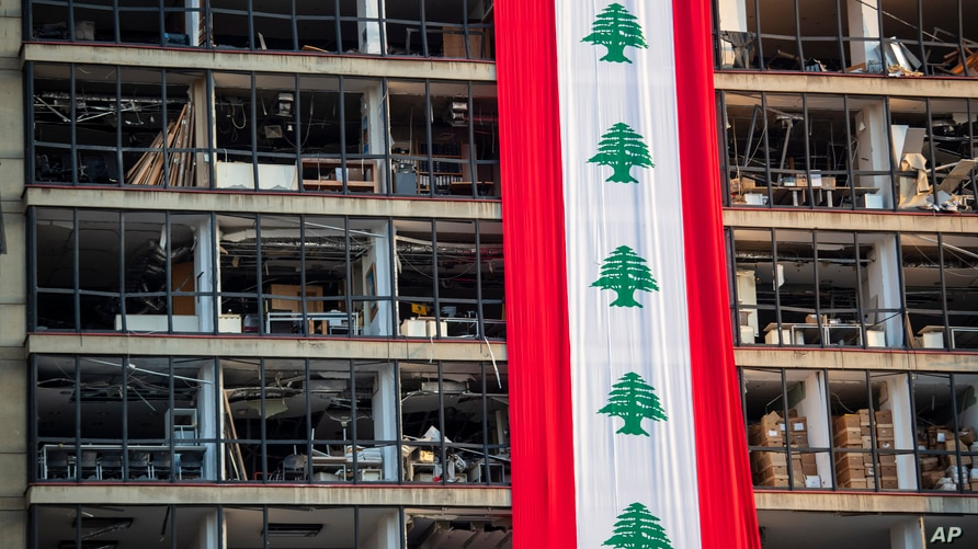 A banner with representations of the Lebanese flag hangs on a damaged building in a neighborhood near the site of last week's…